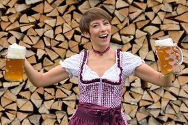 foto of vivacious  - Vivacious woman in a dirndl holding two beers in glass tankards in her hands as she toasts the Oktoberfest stacked woodpile background - JPG