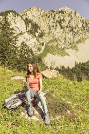 picture of thermos  - Female hiker sitting on a rock taking a break during hiking and holding a thermos in her hand - JPG