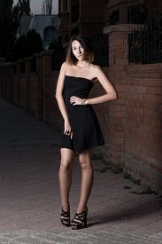 picture of shy woman  - Shy brunette woman in short black dress is posing against red brick wall toned image - JPG