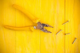 picture of nail-cutter  - Pliers and few nails on the yellow wood surface - JPG