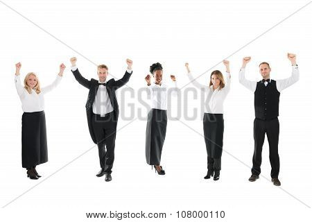 Happy Waiter And Waitresses Standing With Arms Raised