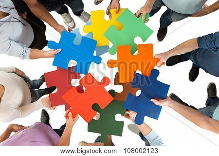 Creative Business People Holding Colorful Puzzle Pieces