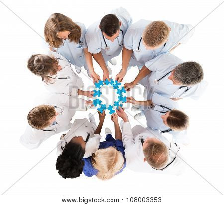 Medical Team Joining Jigsaw Pieces While Standing In Huddle