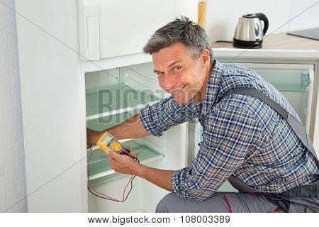 Technician Checking Fridge With Digital Multimeter