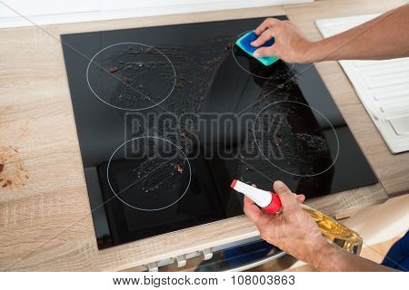 Janitor Cleaning Induction Stove In Kitchen