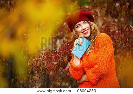 Lovely Girl In A Beret And A Sweater In Autumn Park, Holding A Notebook.