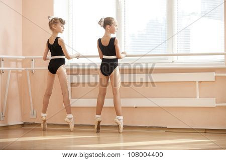 Young ballerinas standing on poite at barre.