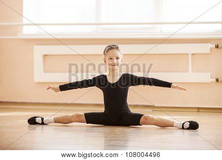 Boy dancer doing splits while warming up.