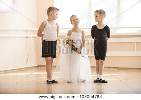 At ballet dancing class: young boys and a girl with flowers.