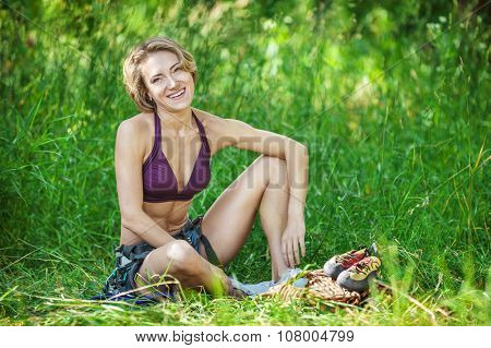 Cheerful rock climber in safety harness relaxing while sitting on grass.