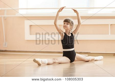 Young girl doing splits while warming up.