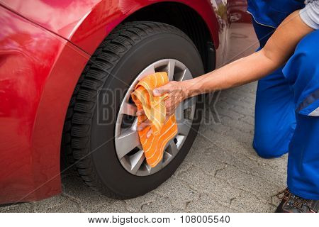 Worker Cleaning Car Wheel