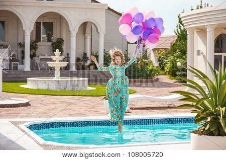 Joyful young woman jumping into the pool while holding a bunch of balloons. Herson, Ukraine