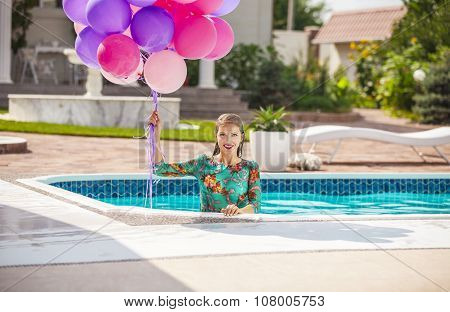 Happy young woman a bunch of balloons after jumping into a swimming pool in a dress.