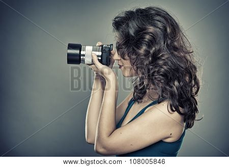 Woman With Photo Camera In A Studio