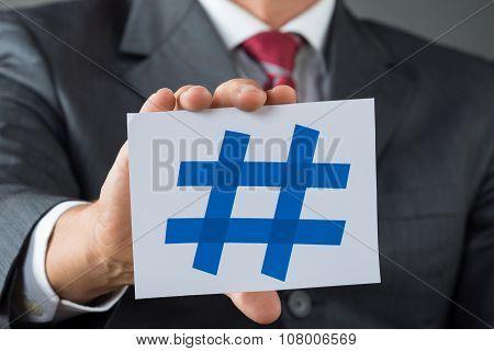 Businessman Showing Hash Sign At Desk