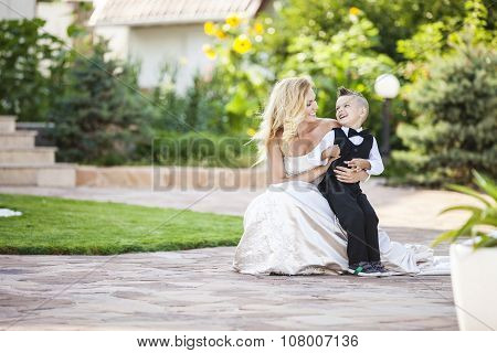 Happy bride and smiling little boy outdoors