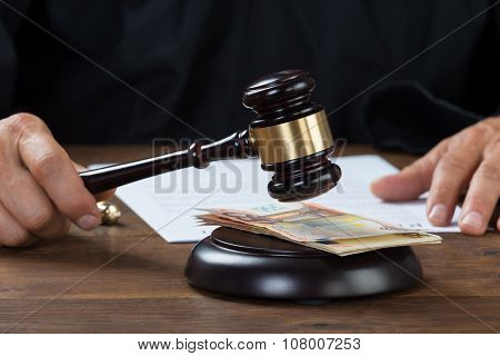Judge Holding Gavel Over Banknotes At Desk