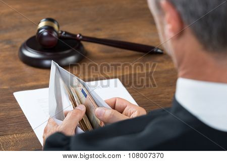 Judge Counting Money In Envelop At Table