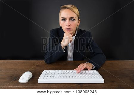 Serious Businesswoman Using Computer Mouse And Keyboard On Desk