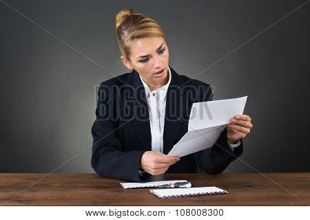 Shocked Businesswoman Reading Letter At Desk