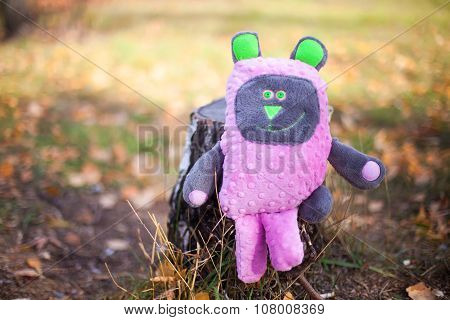 Pink teddy bear with green eyes and ears
