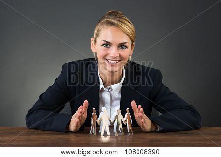 Businesswoman Sheltering Paper Team On Desk