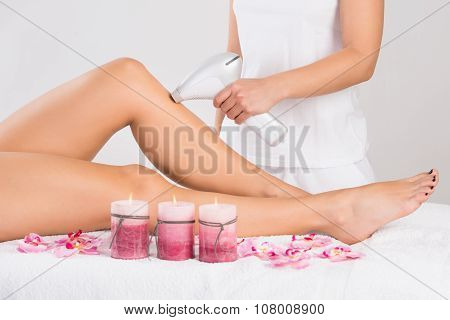 Young Woman Getting Laser Treatment On Leg At Spa