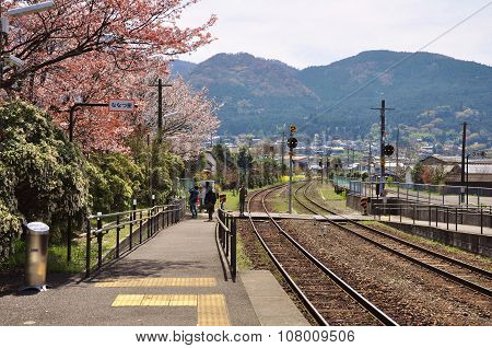railway at Yufuin train station with cherry blossom (sakura) and mountain background.