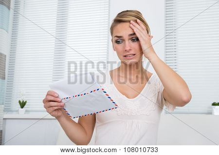 Shocked Woman Reading Letter At Home