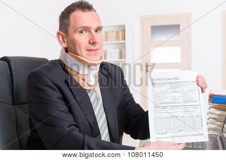 Businessman at work wearing neck brace with insurance claim form in hands