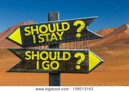 Should I Stay? Should I Go? signpost in a desert background