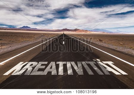 Creativity (in German) written on desert road