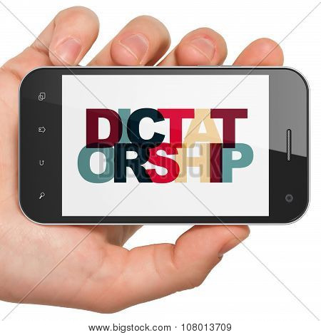 Political concept: Hand Holding Smartphone with Dictatorship on  display