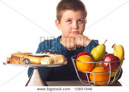 Boy Thinking Over A Healthy Snack Or A Dessert