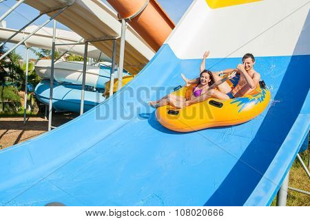 Couple Sliding Down A Water Slide