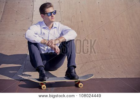 Yound caucasian business man relaxing on skateboard .