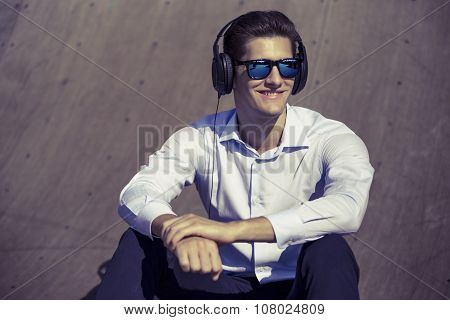 Addicted to music. image of funny business man listening African thru heaphones and smiling in outdo