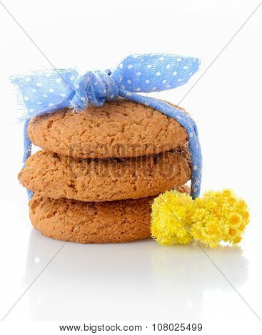 Stack of three homemade oatmeal cookies tied with blue ribbon in small white polka dots and tiny yel