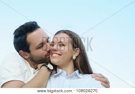 Boy Kissing His Girl's Cheek Outdoors On Blue Sky Background