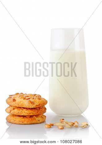Stack of three homemade peanut butter cookies peanuts ear of oats and glass of milk