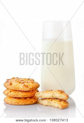Stack of three homemade peanut butter cookies halves of cookies and glass of milk