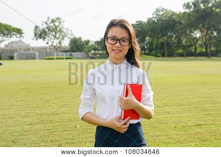 Young and happy female student reads book on grass field