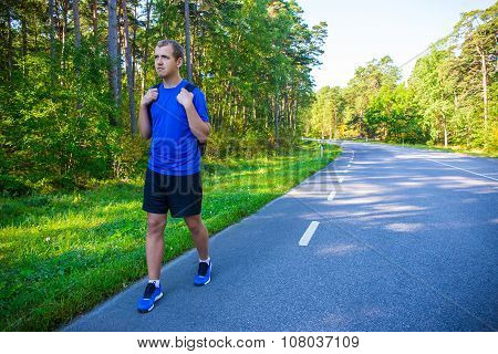 Male Hiker With Backpack Walking Alone On Forest Road