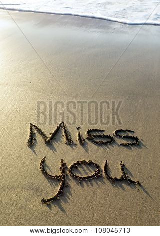 Miss you written in sand with