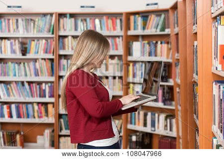 Young Student Using Her Laptop In A Library