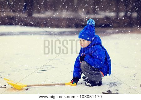 little boy dig and play in winter snow