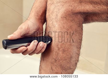 closeup of a young caucasian man trimming the hair of his legs with an electric trimmer