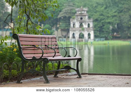 Autumn view of lake, tree and bench on the bank of Hoan Kiem (Sword) lake in Hanoi, Vietnam.