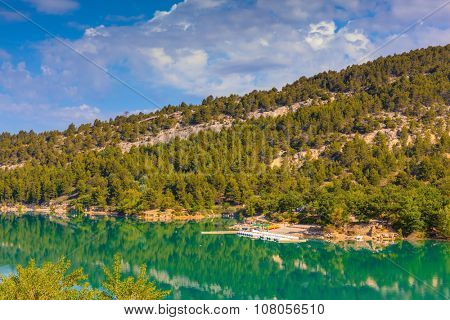 Smooth water of the river reflects the wooded shore and cloudy sky. Europe's largest alpine canyon Verdon